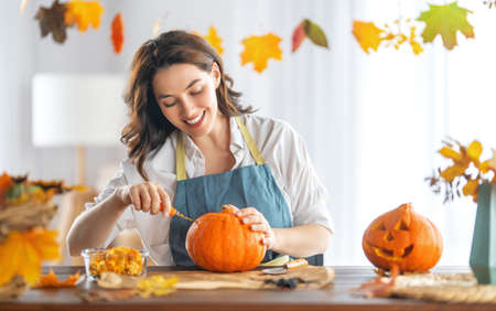 Happy Halloween! Young woman is carving pumpkin. Family preparing for holiday. 免版税图像
