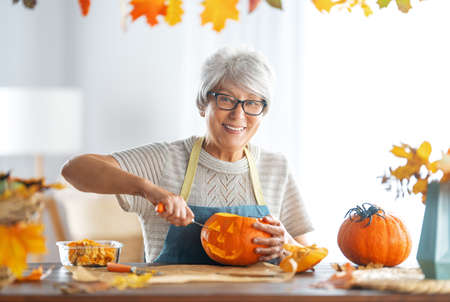 Happy Halloween! Senior woman is carving pumpkin. Family preparing for holiday.