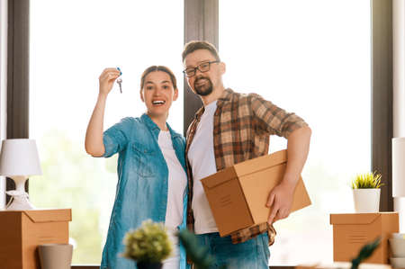 Happy young married couple are moving to new apartment. 免版税图像