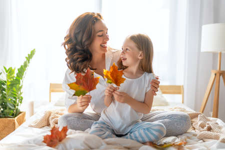 A nice girl and her mother enjoying sunny morning. Good time at home. Child wakes up from sleep. Family playing on the bed in the bedroom. 免版税图像