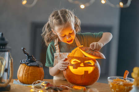 Cute little child girl with carving pumpkin. Happy family preparing for Halloween. 免版税图像