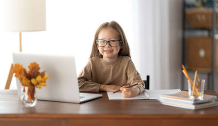 Back to school. Happy child is sitting at desk. Girl doing homework or online education.