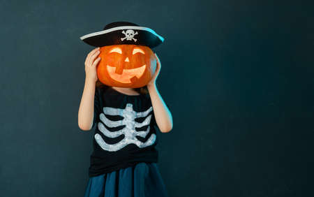 Happy Halloween! Cute little laughing girl in pirate costume on black wall background.