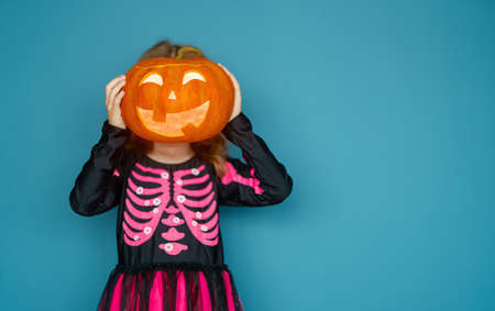 Happy Halloween! Cute little laughing girl in witch costume on blue wall background. 免版税图像