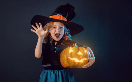 Happy Halloween! Cute little laughing girl in witch costume on black wall background.