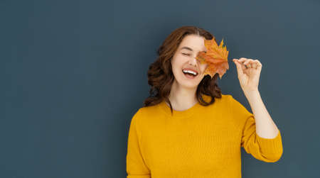 Happy emotional young woman laughing with yellow leaf on dark wall background.