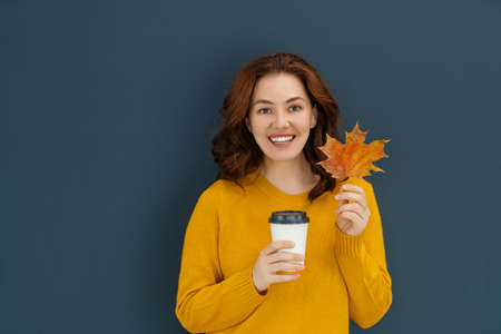 Happy emotional young woman drinking tea on dark wall background. 免版税图像