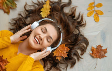 Cheerful young woman listening to music in headphones. Top view. Autumn atmosphere.
