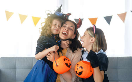 Happy family preparing for Halloween. Mother and children in carnival costumes at home. 免版税图像