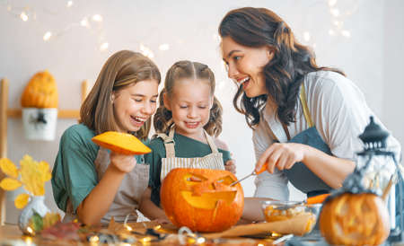 Happy Halloween! Mother and her daughters carving pumpkin. Family preparing for holiday.