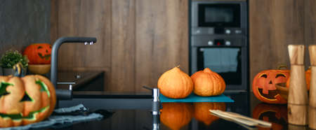 Carving pumpkin on the table at home. Happy family preparing for Halloween.