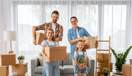 Happy young family are moving to new apartment. Parents and daughters with boxes. 免版税图像