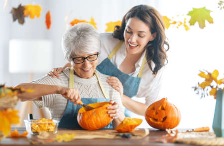 Happy Halloween! Mother and her adult daughter carving pumpkin. Family preparing for holiday.