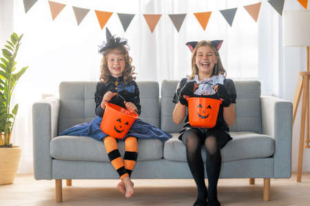 Cute little children girls in carnival costumes. Happy family preparing for Halloween. Funny kids at home.