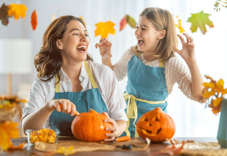 Happy Halloween! Mother and her daughter carving pumpkin. Family preparing for holiday. 免版税图像