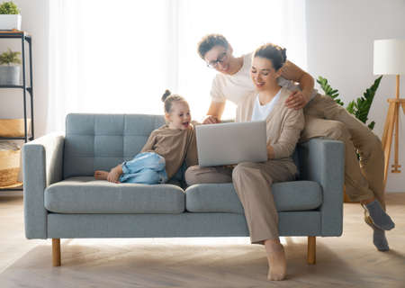 Happy loving family. Young mother, father and daughter using laptop. Funny mom, dad and lovely child are having fun staying at home.