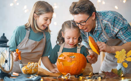 Happy Halloween! Father and her daughters carving pumpkin. Family preparing for holiday.