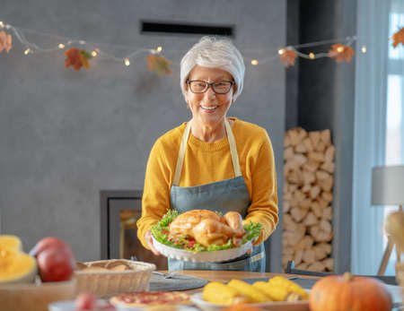 Thanksgiving Day, Autumn feast. Traditional dinner. Senior woman inviting to the table. Фото со стока
