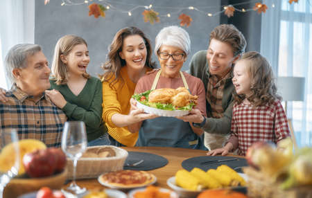 Thanksgiving Day, Autumn feast. Happy family sitting at the table and celebrating holiday. Grandparents, mother, father and children. Traditional dinner. Фото со стока