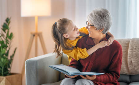 Grandmother reading a book to her granddaughter. Family holiday and togetherness.