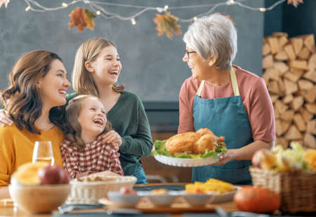 Thanksgiving Day, Autumn feast. Happy family sitting at the table and celebrating holiday. Traditional dinner. Grandmother, mother and daughters.