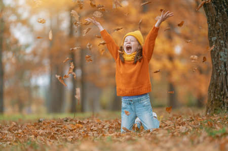 Happy child on autumn walk! Kid walking in the Park and enjoying the beautiful nature. Фото со стока