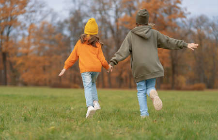 Happy family on autumn walk! Kids walking in the Park and enjoying the beautiful nature.