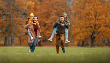 Happy family on autumn walk! Mother, father and daughters walking in the Park and enjoying the beautiful nature.