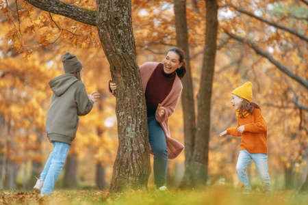 Happy family on autumn walk! Mother and daughters walking in the Park and enjoying the beautiful nature. Фото со стока