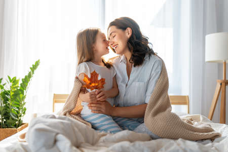 A nice girl and her mother enjoying sunny morning. Good time at home. Child wakes up from sleep. Family playing on the bed in the bedroom. Фото со стока