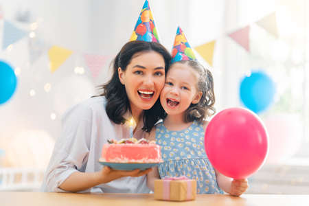 The kid is blowing out the candles on the cake. Mother and daughter are celebrating birthday. Фото со стока