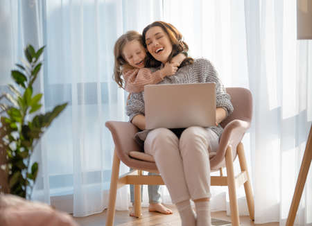 Happy loving family. Young mother and daughter girl using laptop. Funny mom and lovely child are having fun staying at home.