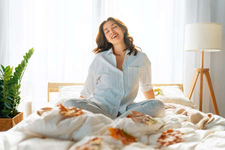 Happy young woman enjoying sunny morning on the bed.