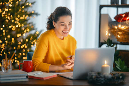 Woman is working in home office decorated for Christmas. Фото со стока