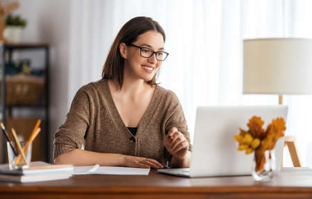 Happy young woman working online, watching webinar, podcast on laptop, having remote conversation at home. Фото со стока