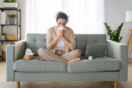 Ill upset girl is holding paper tissue and blowing nose. Virus symptom concept.