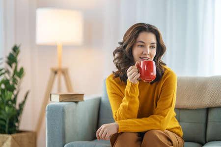 Beautiful young woman enjoying tea sitting on the sofa at home. Фото со стока