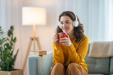 Cheerful young woman listening to music in headphones sitting on the sofa in the room at home.
