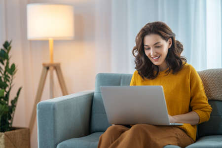 Happy casual beautiful woman using laptop at home. Фото со стока