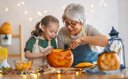 Happy family preparing for Halloween. Grandmother and granddaughter carving pumpkins at home.