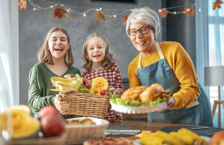 Thanksgiving Day, Autumn feast. Happy family sitting at the table and celebrating holiday. Traditional dinner. Grandmother and granddaughters.