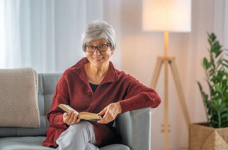 Senior woman sitting on the sofa and reading a book in the room at home.