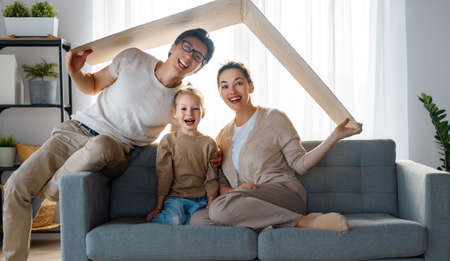 Mother, father and child girl in the room with a symbol of roof. Concept of housing for young family. Фото со стока
