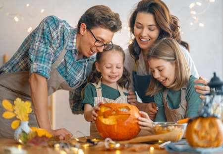 Mother, father and their daughters having fun at home. Happy Family preparing for Halloween.