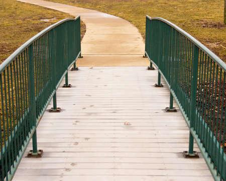 Foot bridge leading to a curved path. Фото со стока
