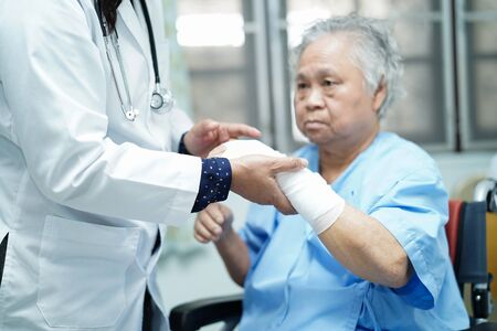 Asian senior or elderly old lady woman patient accident at arm knee with bandage on bed in nursing hospital ward : healthy strong medical concept.