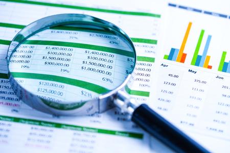 Lupa en papel de hoja de cálculo de gráficos gráficos. Desarrollo financiero, cuenta bancaria, estadísticas, economía de datos de investigación analítica de inversiones, comercio bursátil, concepto de reunión de empresa de oficina de negocios.