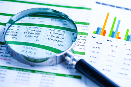 Lupe auf Diagrammen Diagramme Tabellenkalkulationspapier. Finanzielle Entwicklung, Bankkonto, Statistik, investitionsanalytische Forschungsdatenwirtschaft, Börsenhandel, Geschäftsbüro-Firmentagungskonzept.