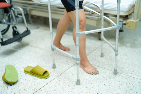 Asian middle-aged lady woman patient walk with walker at nursing hospital ward : healthy strong medical concept
