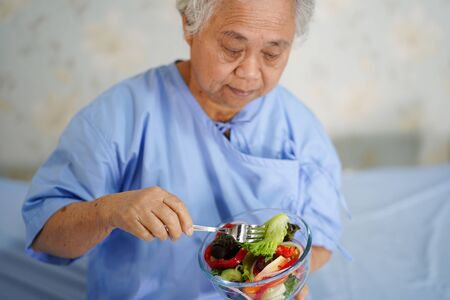 Asian senior or elderly old lady woman patient eating breakfast healthy food with hope and happy while sitting and hungry on bed in hospital. Stock Photo